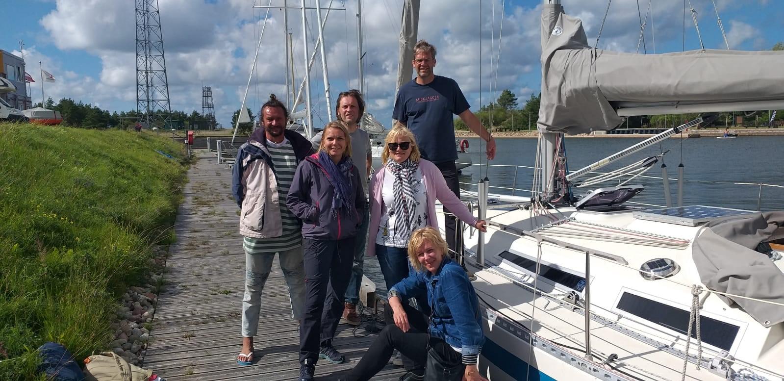 BEF Latvia team standing next to yacht